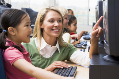 teacher assisting child on using computer
